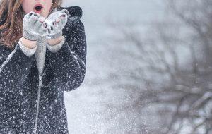 Frau steht im Schnee und pustet in ihre Hände