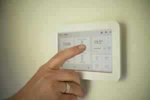 Eine Hand berührt ein modernes Thermostat