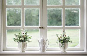 Zwei weiße Fenster mit Blumen auf der Fensterbank