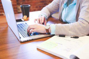 Eine Person arbeitet mit Laptop und Plänen