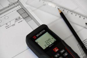 Ein Messgerät liegt auf Bauplänen