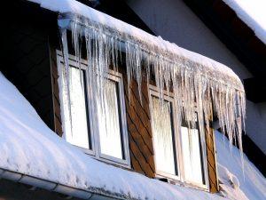 Eiszapfen und Schnee an einem Dach im Winter